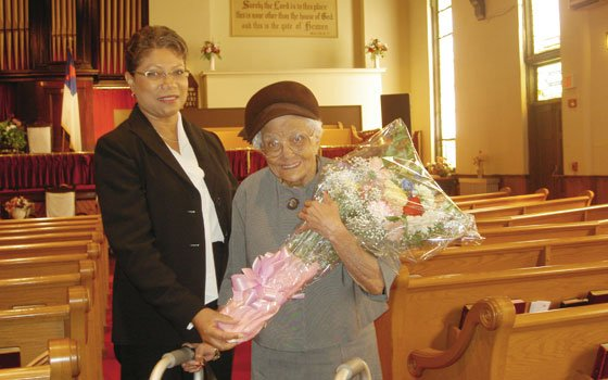 Gertrude Smith (right) holds a bouquet of flowers given to her by members of the Ebenezer...