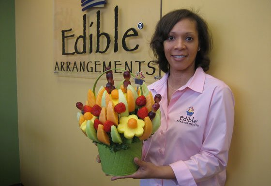 Edible Arrangements franchise owner Toya Farrar holds one of her fruit creations in her South Boston store. Farrar...