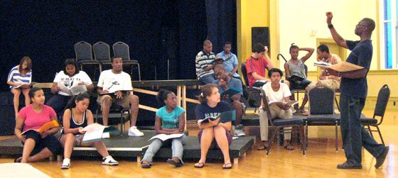 Students listen as Sam Martinborough (right, standing) explains the staging for the performance that will top off a...