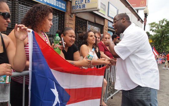 City Councilor Felix Arroyo greets future voter Avi Gonzalez as Michelle Colon and Amaya Hernandez look on during the 45th annual Puerto Rican Festival Parade.