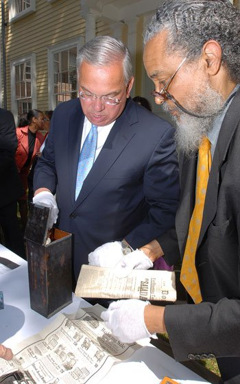 Wearing latex gloves, Mayor Thomas M. Menino (left) and state...