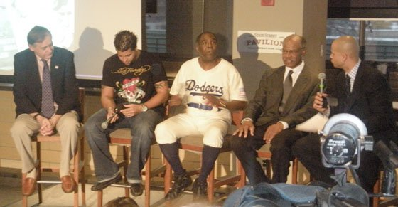 """Gregory Gibson Kenney (center), a member of the National Baseball Hall of Fame Education and Advisory Board and an actor who re-enacts scenes from the life of Jackie Robinson, talks during a panel discussion held at Fenway Park on Jan. 30, 2009, to celebrate Robinson's life and legacy. Joining Kenney were (from left) Ted Spencer, vice president and chief curator of the Hall of Fame; Boston Red Sox pitcher Manny Delcarmen; former Red Sox outfielder Tommy Harper, now a player development consultant for the team; and Cole Wright, NESN """"Sportsdesk"""" anchor."""