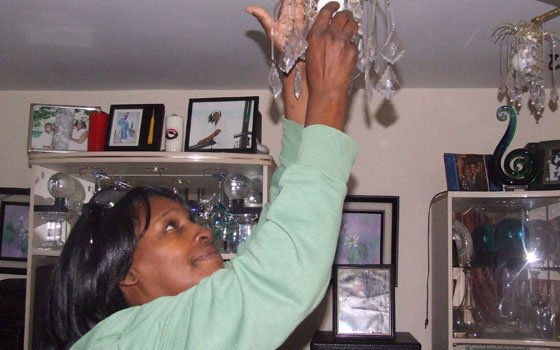Elsie Brown, a resident of the Madison Park Village housing complex in Roxbury, installs a compact fluorescent light...