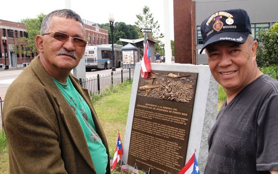 Vietnam veterans Jaime Rodriguez and Tony Molina are planning a memorial for Puerto Rican war veterans in the South End. The plaque between the men, dedicated to the all-Puerto Rican 65th Infantry Regiment, was the first memorial to Puerto Rican veterans in the United States.