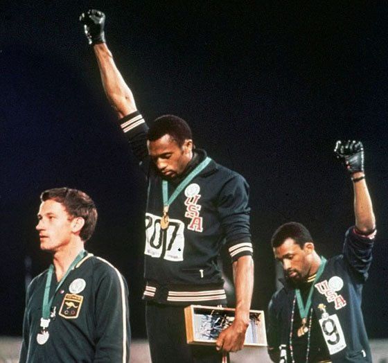 In this Oct. 16, 1968, file photo, extending gloved hands skyward, U.S. athletes Tommie Smith (center) and John...