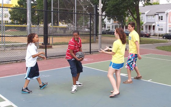 Jermaine Fernandez, 10, and Antonio Martin, 11, shoot hoops at Orchard Gardens with intern Ana Mascagni and Resource...
