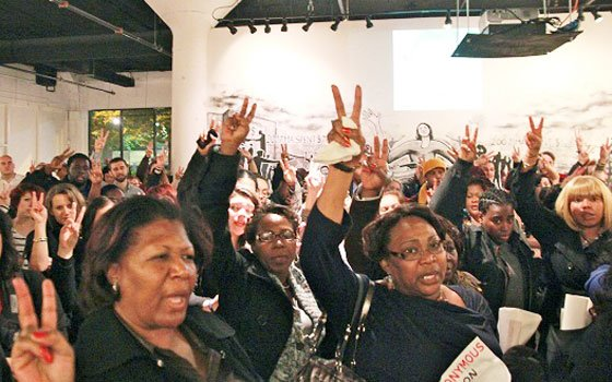 Visitors wave peace signs at the opening night of Anonymous Boston's exhibit at The Fourth Wall Gallery in...