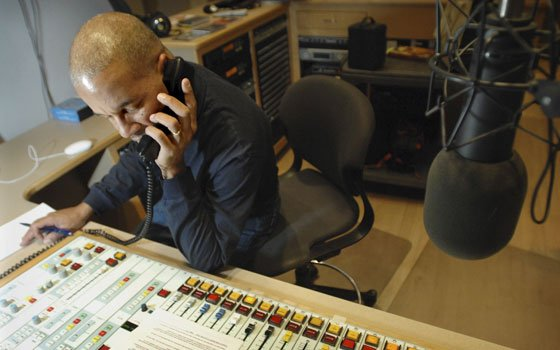 "Radio host José Massó takes a phone call from a listener during the bilingual ""¡Con Salsa!"" radio show..."