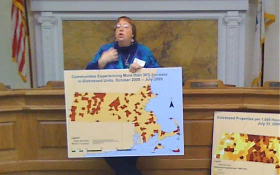 Grace Ross of Mass Alliance Against Predatory Lending shows a map of the hardest-hit areas in the statewide...