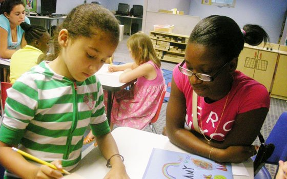 Dacia Jordan (r), 15, watches Leslie Roman, 9, as she works diligently on a self-esteem exercise at last...