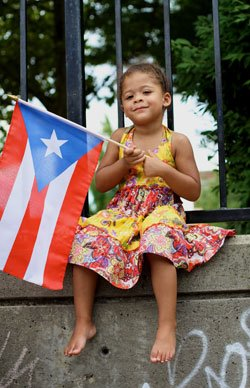 A young girl waves a Puerto Rican flag during last...
