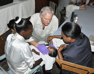 A few days after the earthquake struck in Haiti, S. Allen Counter, a Harvard professor and neurophysiologist, organized the first of his two earthquake relief efforts. Through his friendship with Dominican Republic President Leonel Fernandez Reyna , Counter was able to secure helicopters to transport much-needed medical supplies and about 150-family-sized tents. A dozen of those tents were donated by children of the Mariah Baldwin Elementary School of Cambridge. The medical team included of Dr. Bruce Price, Chief of Neurology and Psychiatry at Massachusetts General Hospital (shown treating an infant
