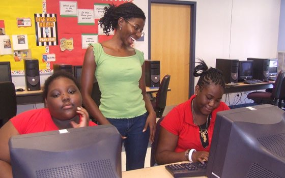 Good News program coordinator Nicole Daley (standing) gives writing advice to Francesca Durocher (left) and Ieysha Smith (right) on Saturday, Aug. 1, 2009, at Mildred Avenue Community Center in Mattapan.