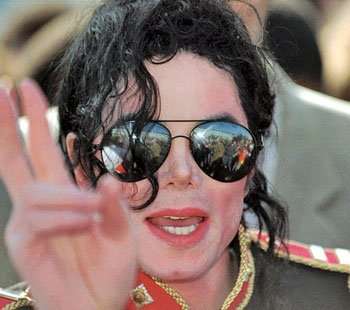 Michael Jackson waves to fans after arriving at Johannesburg International Airport in...