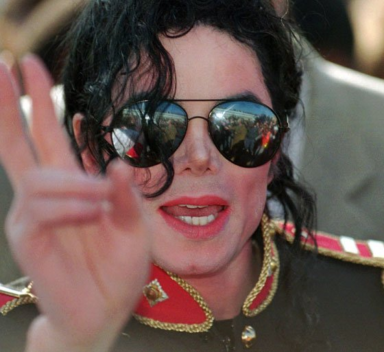 Michael Jackson waves to fans after arriving at Johannesburg International Airport in South Africa on Thursday, July 18,...