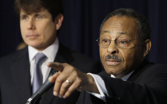 Former Illinois Attorney General Roland Burris (right) speaks as Illinois Gov. Rod Blagojevich looks on during a news...