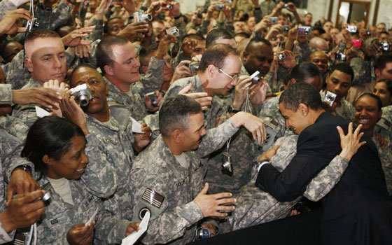 President Barack Obama hugs military personnel at Camp Victory in Baghdad, Iraq, on Tuesday, April 7, 2009. Obama...