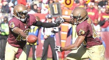 Washington's quarterback Robert Griffin III (10) hands off to Washington's running back Alfred Morris (46)...