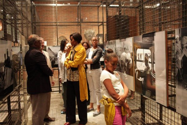 First Lady Michelle Obama, accompanied by her daughters and her mother, visited the Nelson Mandela Foundation and was given a tour by Graca Machel, Mandela's wife, of an exhibit chronicling the 27 years Mandela was imprisoned at Robben Island. / Courtesy photo
