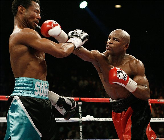 Six-Time World Champion Floyd Mayweather (right) throws a right hand en route...