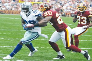 Dallas WR Dez Bryant (88) catches a pass, evades Redskins Oshiomogho Atogwe (20) and runs into the end zone to give the Dallas Cowboys their first touchdown of the game. Dallas defeated Redskins 27