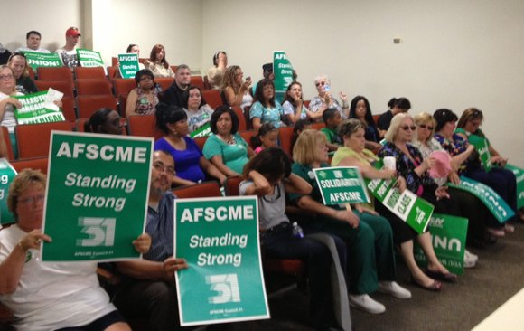 """Carrying signs that read """"Stand up for the Middle Class"""" and """"AFSCME Standing Strong,"""" hundreds of union employees gathered inside ..."""