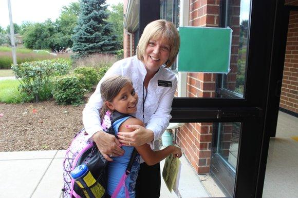 "Fourth-grader Sophia Sanchez gets a big ""welcome back"" hug from Jonas Salk Elementary School Principal Michele Romolt."