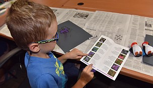 """A student reads the guide """"Wildflowers and Grasses of Midewin."""" The guide is one of many tools and resources for learning about natural resources and conservation that are available on the Midewin website."""