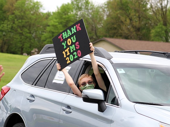 An Indian Trail Middle School student holds a sign as he drives by a line of teachers wishing him well ...