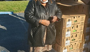 Ora Holloway of Igniting The Fire Prayer Center stands ready and waiting for families to pick up a holiday Thanksgiving basket.