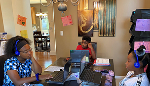 Siblings from Plainfield gather around the dining room table for a remote learning session.