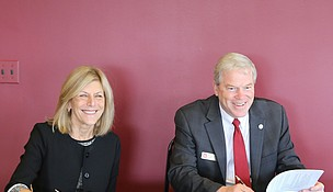 Ruth Colby, President and CEO of Silver Cross Hospital, and Dr. David Livingston, President of Lewis University, sign a student loan repayment agreement Oct. 22 at Lewis University in Romeoville.