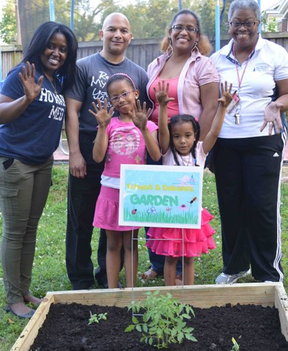 The new gardeners proudly display their soil-covered hands as they christen their garden along with, from left, Stephanie Purnell of Howard, their father, Antonio Evans, mother, Michelle Phillips-Evans, and Dr. Michal Young of Howard University College of Medicine and Howard University Hospital.