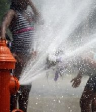 Children cool off in a fire hydrant in Philadelphia during the East Coast heat wave of 2011