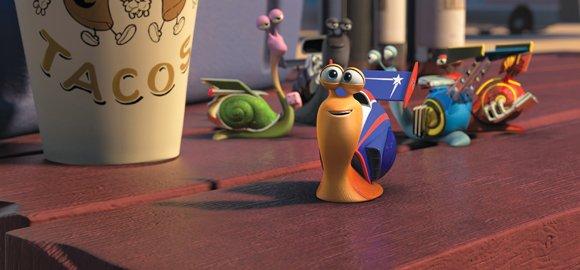 Turbo (foreground, Ryan Reynolds) enjoys the company of his new friends, the Racing Snails (from left): Smoove Move (Snoop Dogg), Whiplash (Samuel L. Jackson), Skidmark (Ben Schwartz) and Burn (Maya Rudolph).