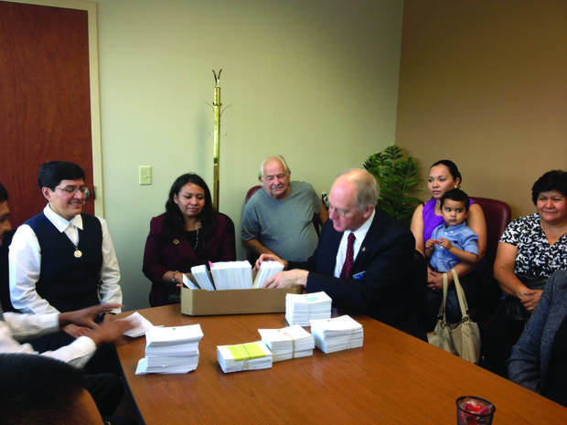 U.S. Rep. Bill Foster (D-Naperville) looks over the petition postcards urging immigration reform that were dropped at his office by members of the New Horizon immigrant-run social ministry group.