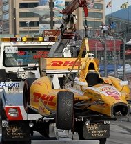 A DHL race car being towed away after an accident