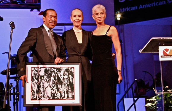 Emmy-award winning artist, Obba Babatundé (left) and Executive Director of the California African American Museum, Charmaine Jefferson (right), present legendary dance icon, Carmen De Lavallade and her husband, Geoffrey Holder (not pictured), with a Lifetime Achievement Award at CAAM's annual gala.