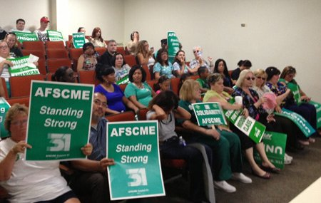 Union employees, carrying picket signs have attended at least two recent county board members to show their solidarity.