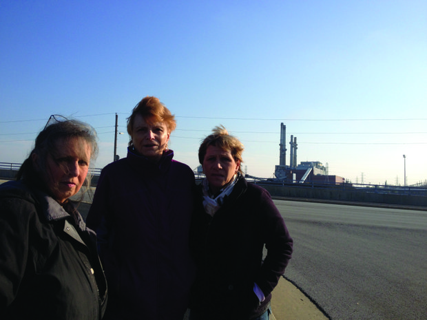 Mary Brucenski (from left), Ellen Rendulich and Mary Burnitz, all members of the Citizens Against Ruining the Environment group, stand across the street from the Midwest Generation coal-fired plant in Romeoville where smoke stacks from the plant loom large in the background.