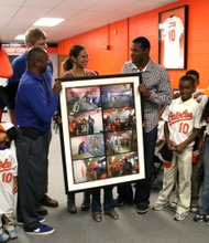 Kenneth R. Darden President/CEO, Boys & Girls Clubs of Metropolitan Baltimore, Inc. presents Adam Jones with a framed collection of photographs of Jones working on the renovations to the building.