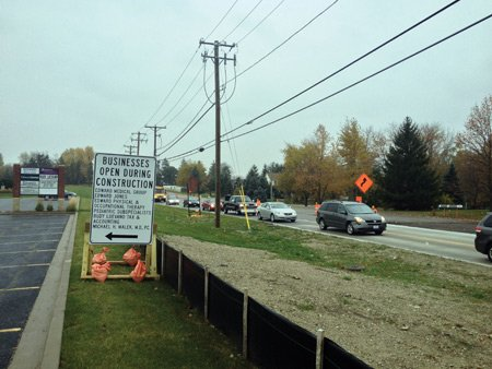 A sign along Weber Road where a major reconstruction project is underway alerts motorists that the businesses remain open while the work progresses.