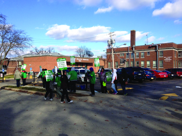 Striking union employees march in front of the Will County Health Department Monday afternoon.