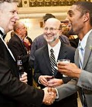 St. Mary's College of Maryland professor Larry Vote, left, shakes hands with Brandon Scott, a 2006 graduate aided by the Baltimore City Scholarship Initiative as former college president, Joseph Urgo, center, looks on.