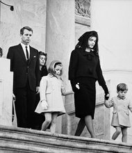 Kennedy family members leaving the funeral ceremony for President John F. Kennedy. Photograph includes: (L-R) Jean Smith, Robert F. Kennedy, Patricia Lawford, Caroline Kennedy, First Lady Jacqueline Kennedy, and John F. Kennedy, Jr. East Front Entrance of Capital Building, Washington, D.C.