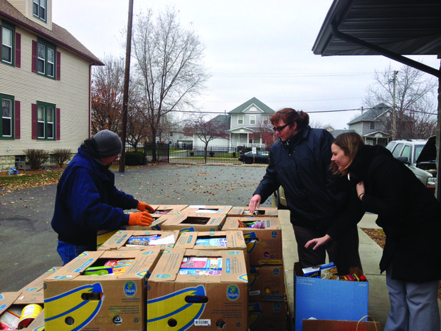 Chris Becker (from left) helps Jackie Kinney, volunteer coordinator at the MorningStar Mission, and Chrissy Brown, the mission's director of development, as they look over boxes of food donated earlier this week for Thanksgiving.