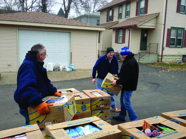 Chris Becker (from left), Dennis Zalesiak and Dennis Gross load boxes of donated food onto pallets earlier this week at the MorningStar Mission.