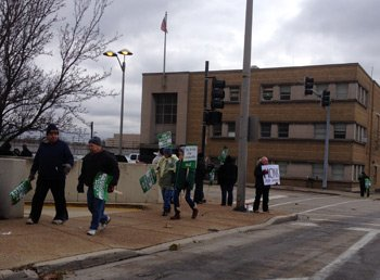Union workers are seen picketing at the Will County Courthouse.