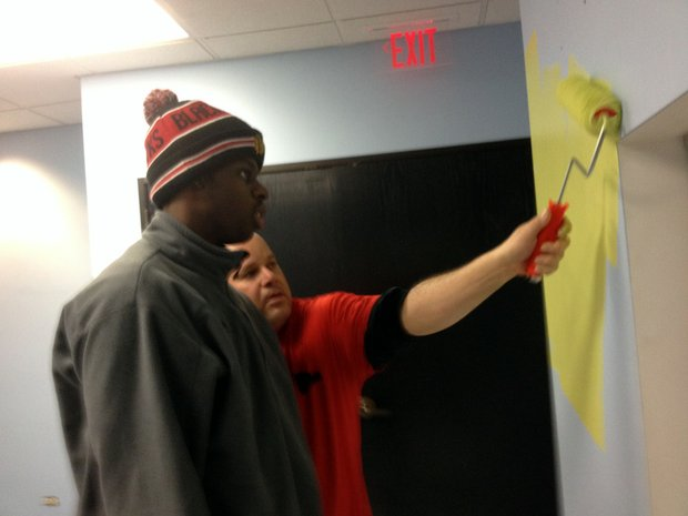 Coordinator Ross Novak shows William Laurence, with the Joliet Job Corps, how to paint while volunteering for the Day of Service at the Child Care Resource and Referral Office in Joliet.