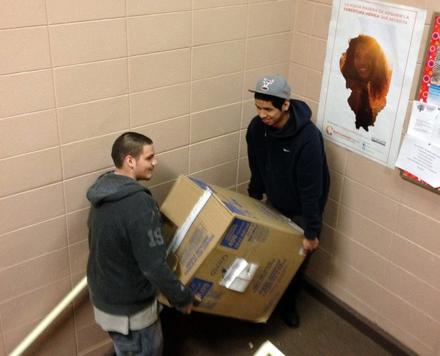 Alex Barrera (left) and Oscar Torres carry a box of food up to the Food Pantry at the Spanish Community Center in Joliet.
